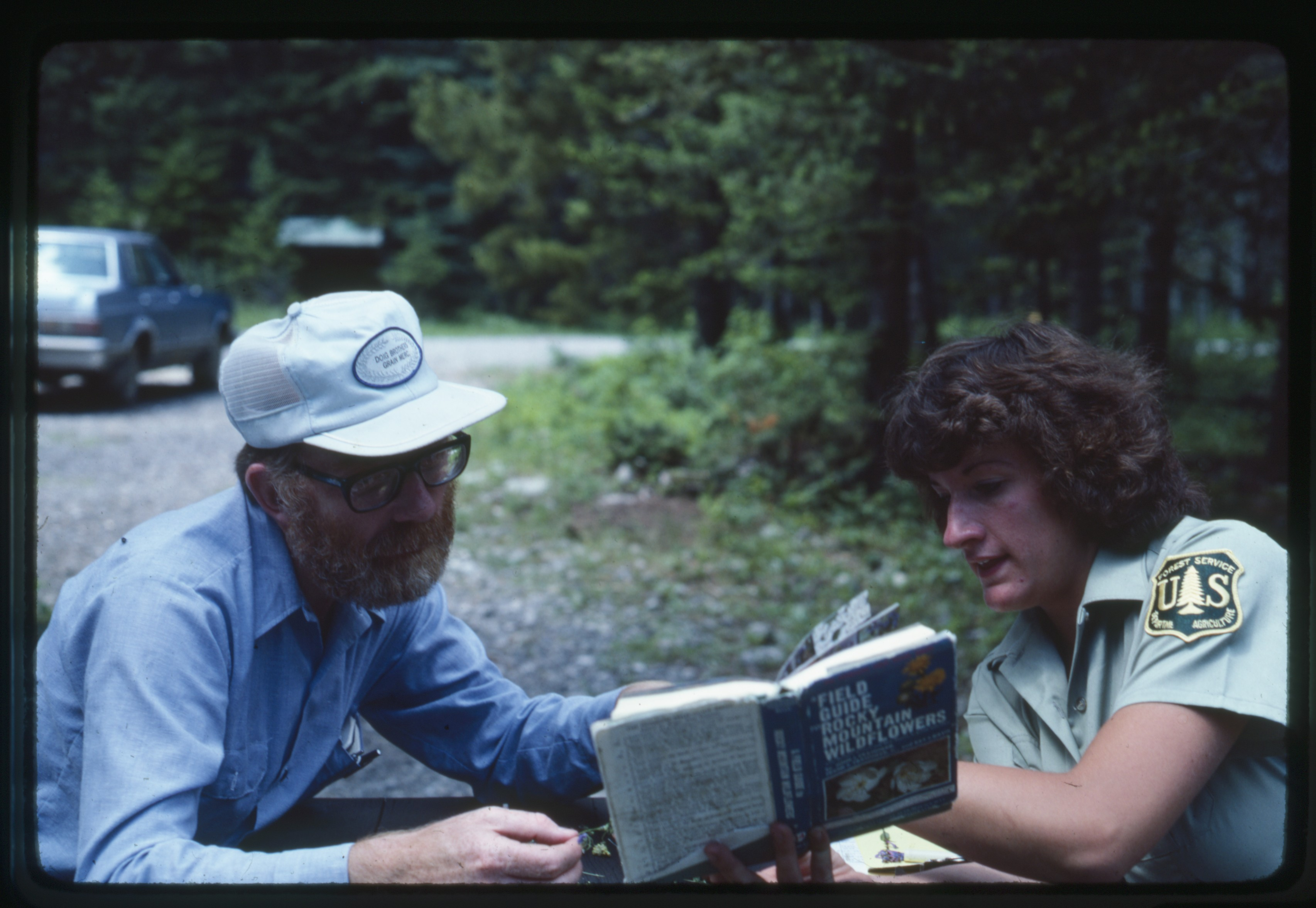 Ivan Doig and Judy Olson examine a book at Cave Mountain campground